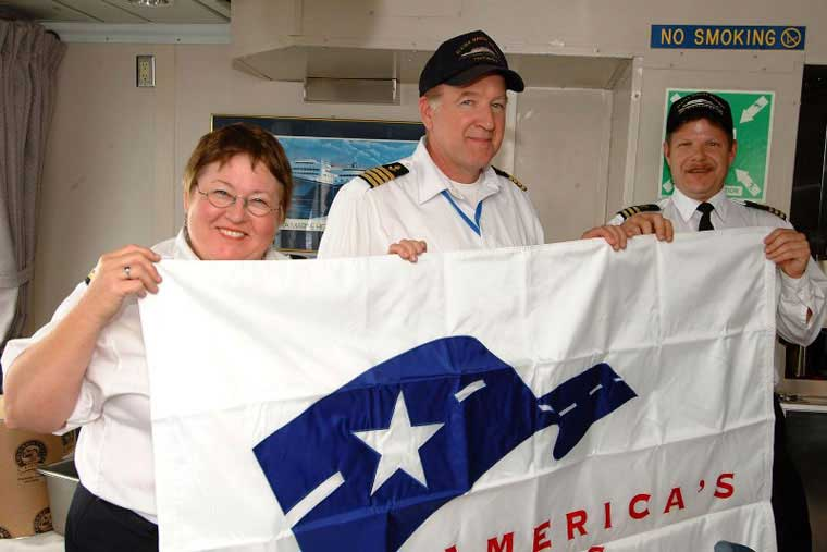 National Scenic Byways Flag aboard <em>MV Tustumena</em> (Left to right: Chief Purser Christy Taylor, Captain JP Stormont, Chief Steward Mark Listberger) &copy; AMHS
