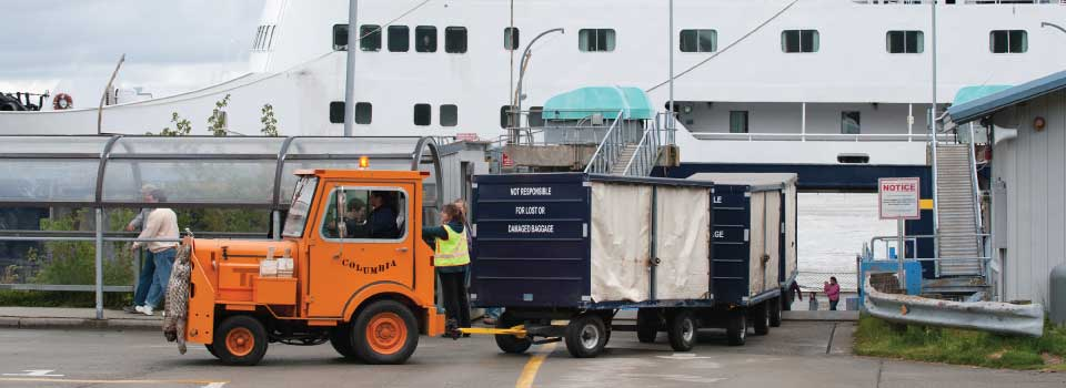 The MV Columbia in port with crew unloading baggage cart © Joshua Roper Photography / Alaska Marine Highway System